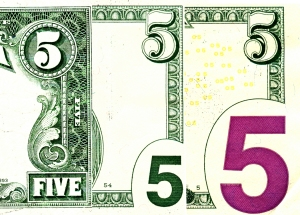 The right edge of three $5 bills, dating from 1985, left, 2003, center, and 2006, right. The border becomes simpler and less well engraved as we get to more modern bills.